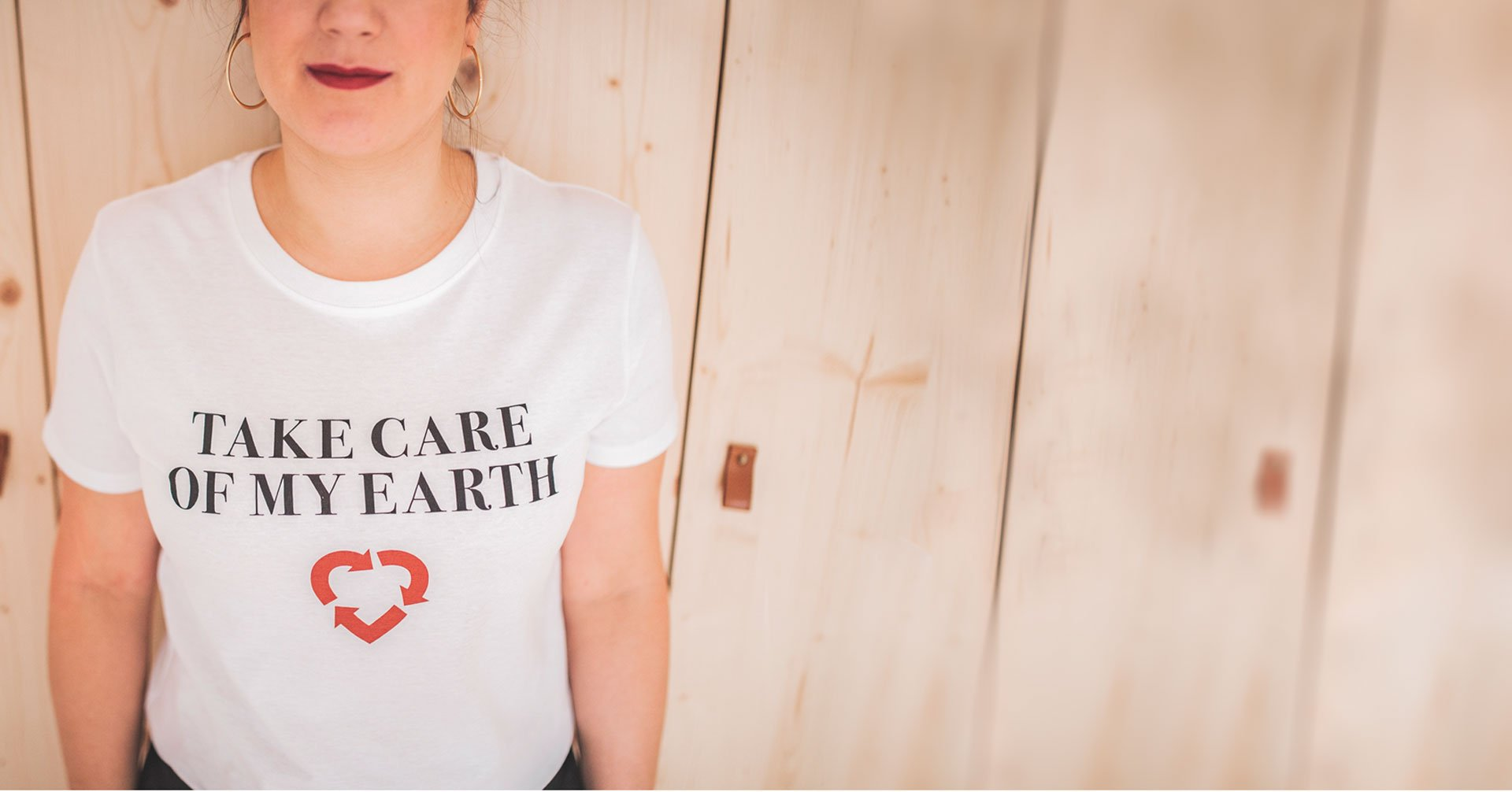 "Torax de una chica con una camiseta blanca que dice ""Take care of my earth"""